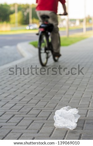 Plastic bag thrown by the bicyclist on the street, littering the city.  - stock photo