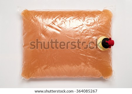 Plastic bag with tap full of apple juice