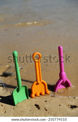Plastic beach shovels in sand on a beach. - stock photo