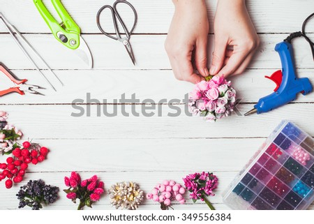 Plastic berries, flowers, beads and instruments for doing handmade decorations and bijouterie. Top view - stock photo