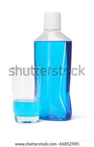 Plastic bottle and glass of mouthwash on white background