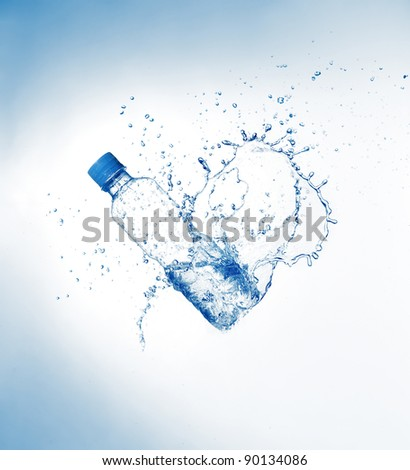 Plastic bottle and water splashes and drops on blue background