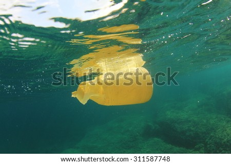 Plastic bottle disposed of in sea causes environmental damage from pollution - stock photo
