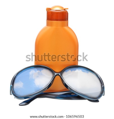 Plastic bottle for sun lotion and black sun glasses with blue sky reflecting, isolated on white.