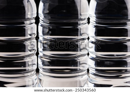 Plastic bottle of drinking water isolated on back, unfocused - stock photo