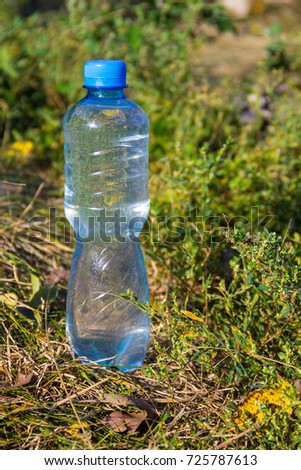 Plastic bottle of drinking water on the ground in forest