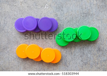 plastic bottle screw caps used to seal plastic bottles, green, orange and violet
