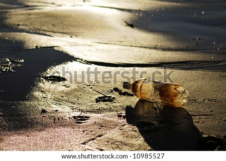Plastic bottle washed up on dirty looking beach - stock photo