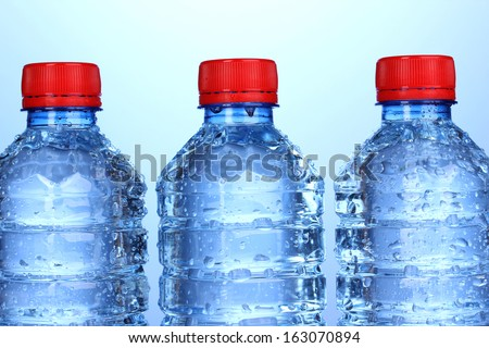 plastic bottles of water on blue background - stock photo