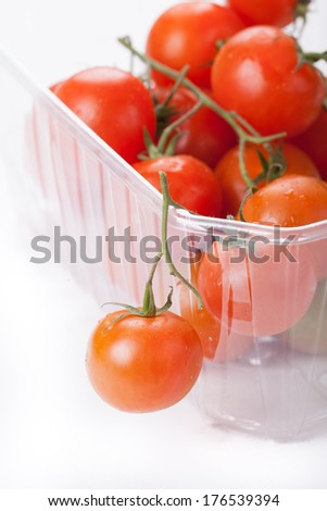 Plastic  box with cherry tomatoes on a white background