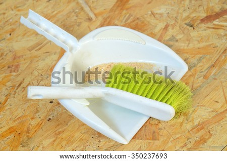 Plastic brush and dustpan with sawdust placed on OSB board