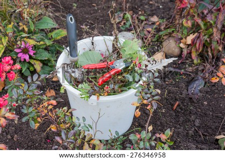 Plastic bucket with garden tools and garden waste - stock photo