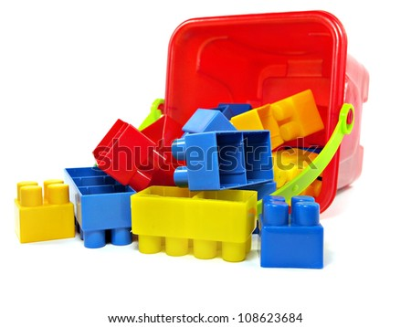 plastic building blocks in red toy pail on a white background - stock photo