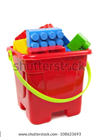 plastic building blocks in red toy pail on a white background