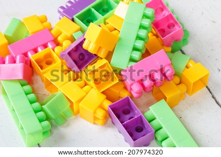 Plastic building blocks on table - stock photo
