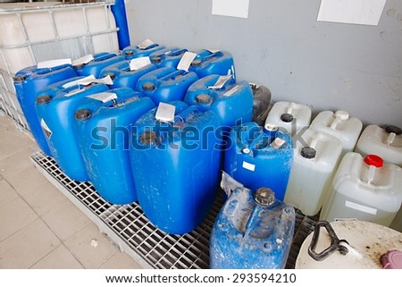 Plastic cans of chemicals in a factory - stock photo