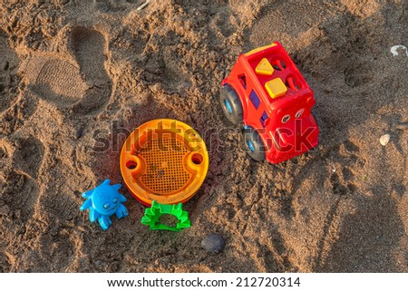 Plastic children toys on the sand beach - stock photo
