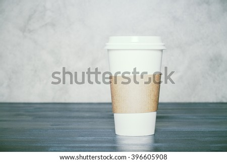 Plastic coffee cup on dark wooden table and concrete background. Mock up - stock photo