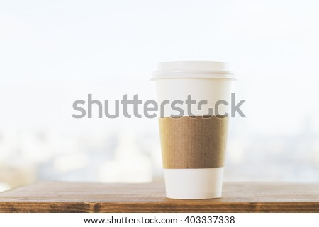 Plastic coffee cup on wooden desktop and blurry white background. Mock up - stock photo