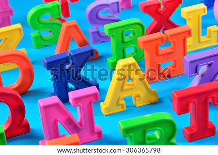 Plastic colorful alphabet letters close up on a blue background