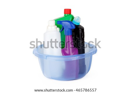 Plastic colorful detergent bottles in laundry basket, isolated on white background.