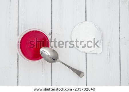 Plastic container for dairy foods with red clear jelly pudding with foil lid and spoon. Isolated on a white. Top view - stock photo