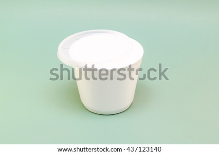plastic container with a lid for food on a green background - stock photo