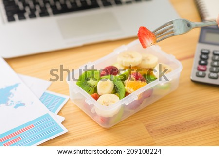 Plastic container with fruit salad and a fork on the desk, selective focus - stock photo