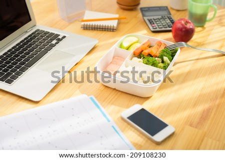 Plastic container with healthy food on the office table - stock photo