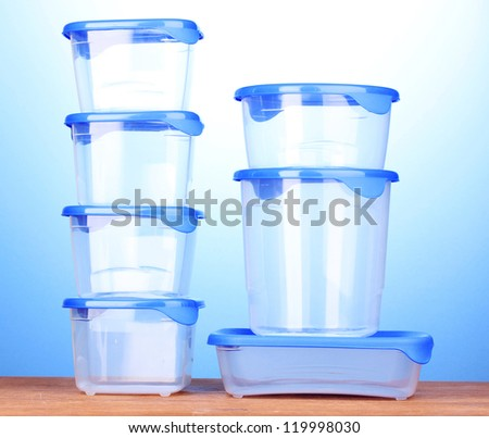 Plastic containers for food on wooden table on blue background - stock photo