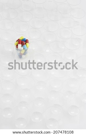 Plastic cup containing pills, surrounded by empty glasses