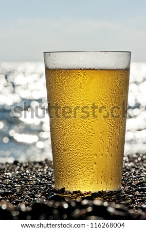 Plastic cup of beer standing on the sand by the sea. - stock photo