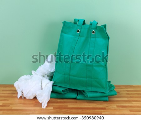 Plastic disposable bags and environmentally friendly re- usable bags with a green wall background - stock photo