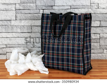 Plastic disposable bags and environmentally friendly re- usable tartan bag with a Stone wall background - stock photo