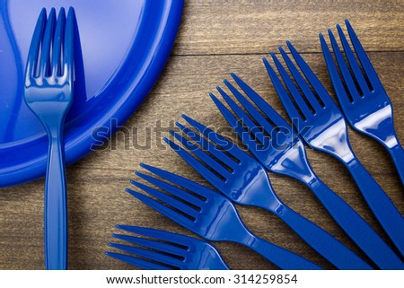Plastic disposable forks and plates for going on a picnic. - stock photo