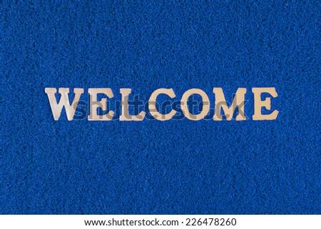 Plastic doormat and welcome word - stock photo