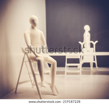 Plastic dummy sitting on the chair. Toned picture - stock photo