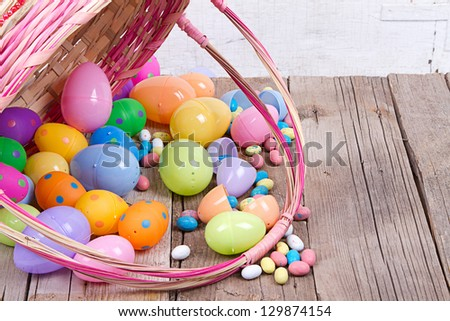 Plastic Easter Eggs By Nest Filled With Candy In A Basket On Wooden Background