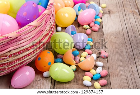 Plastic Easter Eggs Filled With Candy In A Basket On Wooden Background