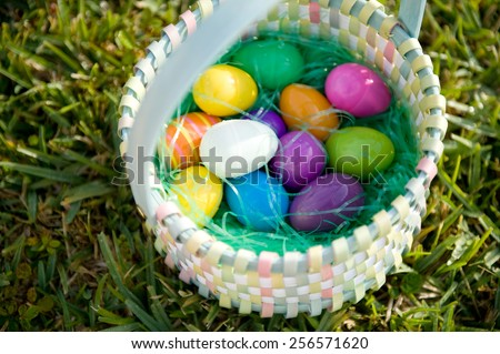 Plastic eggs in an Easter basket outdoors - stock photo