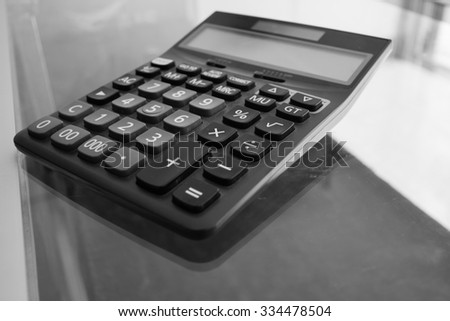 Plastic electronic desk calculator with grey and black keys for accounting or mathematical calculations on a glass table, close-up - stock photo