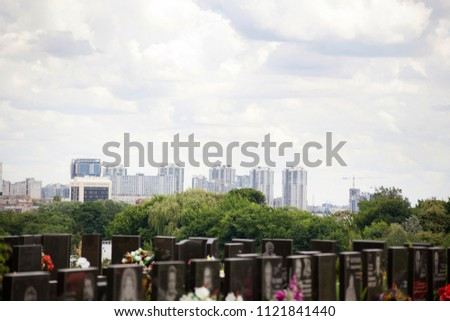 Plastic flowers among the black obelisks of the graves on the background of the city