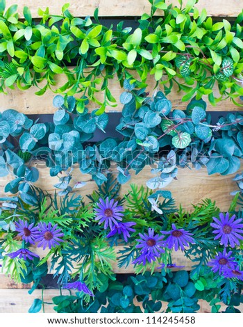 Plastic flowers and plants in wooden pot as vertical garden. - stock photo