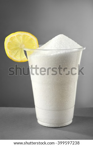 Plastic glass full of sugar with lemon on grey background - stock photo
