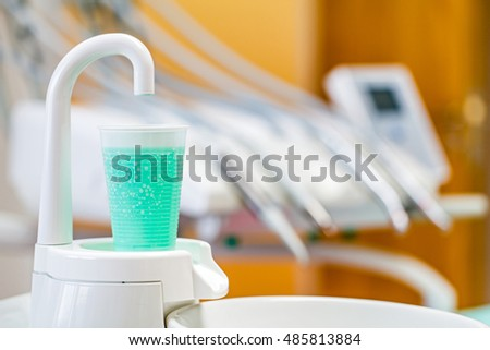 Plastic glass with antiseptic rinsing liquid in the dental cabinet