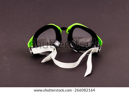 Plastic green goggles for swimming. Located on a black background.