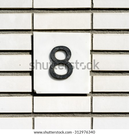 Plastic house number eight on a wall with white glazed bricks - stock photo