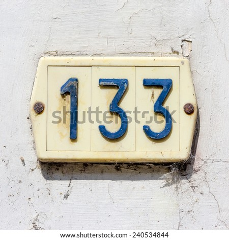 Plastic house number one hundred and thirty three - stock photo