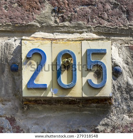 plastic house number two hundred and five - stock photo