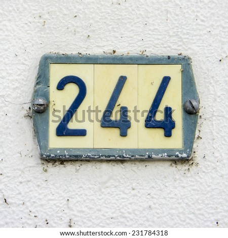 Plastic house number two hundred and forty four. - stock photo